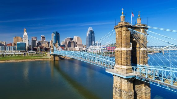 Elevated view of the Roebling Suspension Bridge with Downtown Cincinnati skyline in the background and the Ohio River just below.